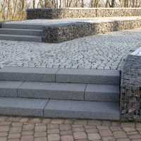 Natursteinmauer mit Gitter und Steinstufen